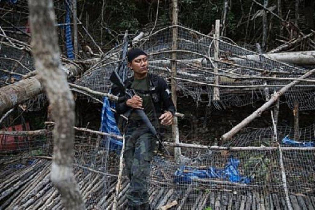 KAWALAN KETAT: Seorang anggota polis mengawal kawasan kem pemerdagangan manusia di kawasan Bukit Wang Burma berhampiran sempadan Malaysia-Thailand. - Foto REUTERS