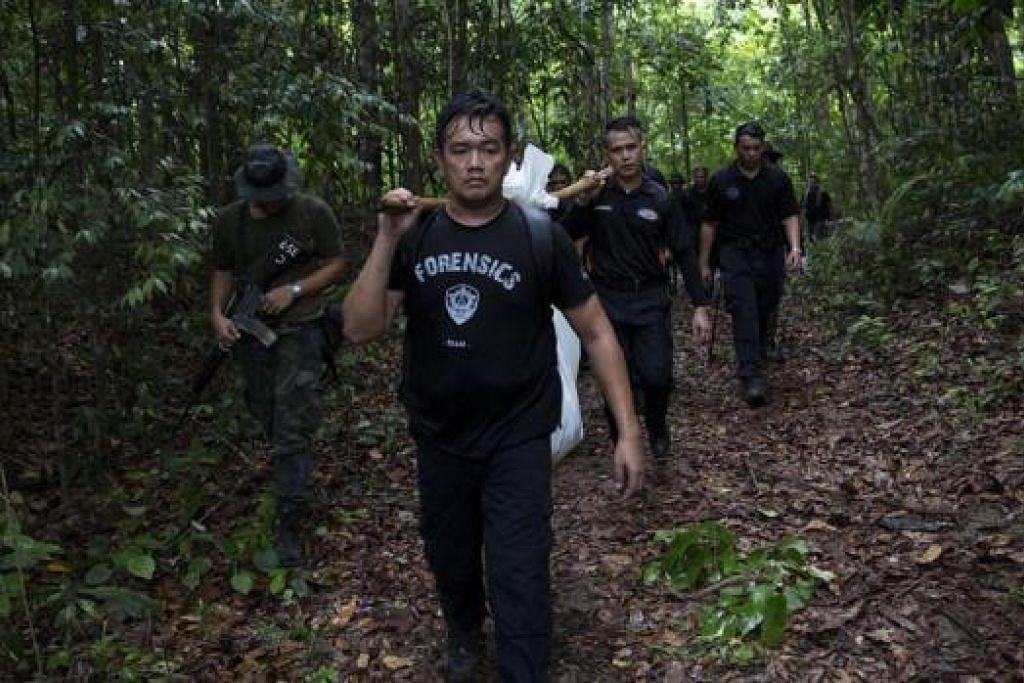 BAWA MAYAT PELARIAN KELUAR HUTAN: Anggota pasukan forensik Polis Diraja Malaysia membawa beg yang mengandungi saki-baki mayat pelarian dekat Bukit Wang Burma, utara Malaysia, semalam. - Foto REUTERS