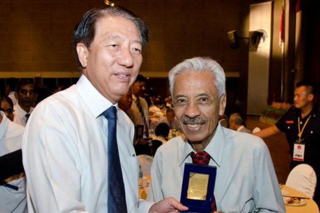 PEGAWAI PERINTIS DIIKTIRAF: Encik Yunnos (kanan), yang telah berkhidmat dengan SCDF selama 41 tahun, menerima medalion peringatan SG50 Home Team, yang diberi kepada pegawai perintis Home Team, daripada Encik Teo semalam. - Foto HOME TEAM NEWS