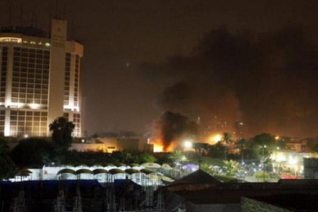 SERANGAN BOM: Api dan asap berkepul-kepul dapat dilihat di tempat meletak kenderaan berdekatan sebuah hotel di Baghdad menyusuli insiden letupan bom kereta di situ. - Foto REUTERS