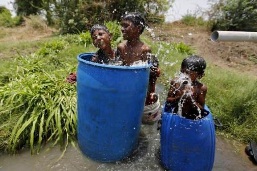 CUBA SEJUKKAN BADAN: Kanak-kanak India di Ahmedabad, India, bermain di dalam baldi besar yang diisi air untuk menyejukkan diri mereka. - Foto REUTERS