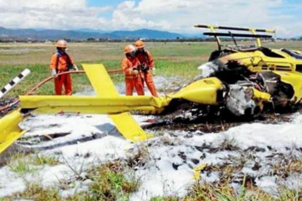 PANTANG MAUT SEBELUM AJAL: Anggota penyelamat memadamkan kebakaran helikopter yang terhempas dan terbakar ketika ingin berlepas di Sabah, kelmarin. Juruterbang pelatih wanita, Cik Fatin Nadeera, bagaimanapun terselamat. - Foto THE STAR