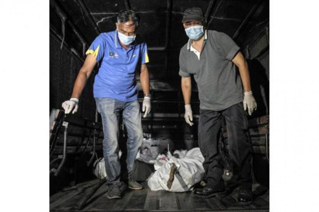 DIBAWA NAIK TRAK: Kakitangan Polis Diraja Malaysia (PDRM) membawa rangka manusia, dipercayai mangsa pemerdagangan manusia, ke dalam trak polis. - Foto AFP