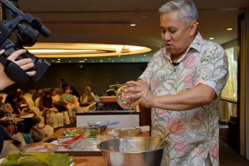 SIAPKAN HIDANGAN: Cef Wan menunjukkan cara memasak otak-otak makanan laut menggunakan daun pisang untuk membungkus isi ikan dan udang sebelum dibakar. - Foto TUKIMAN WARJI