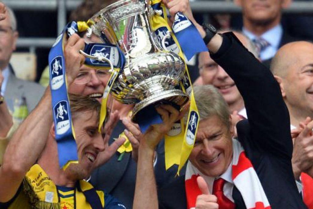 KEJAYAAN BERSEJARAH: Pengurus Arsenal, Arsene Wenger (kanan), menjulang mahkota Piala FA untuk kali keenam sejak beliau memimpin kelab Arsenal itu. Bersamanya ialah pemain pertahanan pasukan, Nacho Monreal. – Foto AFP
