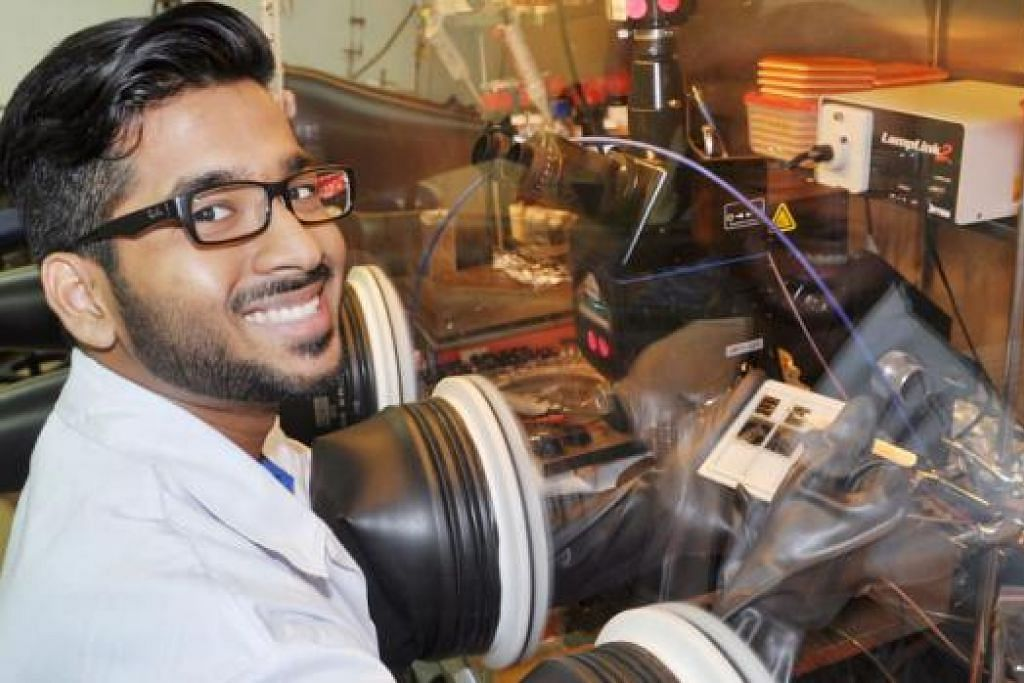 JATUH CINTA DENGAN SAINS: Encik Muhammad Feroz menunjukkan alat 'glovebox' yang mengandungi transistor polimer yang perlu dijaganya semasa menjalani latihan amali di sebuah makmal A*Star. - Foto JOHARI RAHMAT