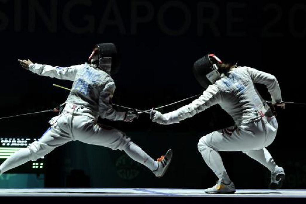DETIK BERSEJARAH: Wang (kanan) menewaskan Gail dari Filipina dalam final acara lawan pedang foil perseorangan wanita bagi memenangi pingat emas pertama Team Singapore.