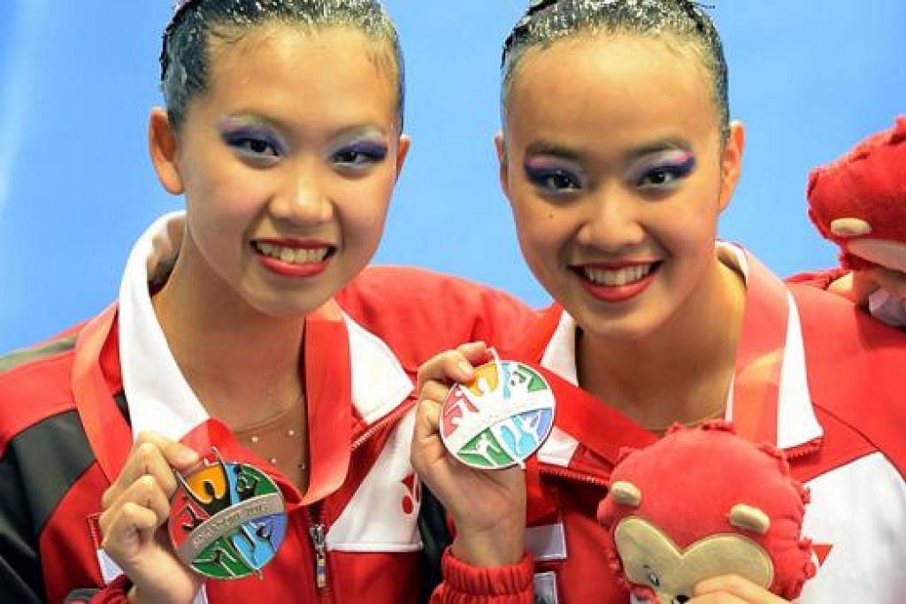 KALAH TIPIS: Stephanie Chen Mei Qi (kanan) dan Crystal Yap Yu Hui dengan pingat perak yang mereka menangi pada acara renang berirama duet semalam. - Foto ZAINAL YAHYA