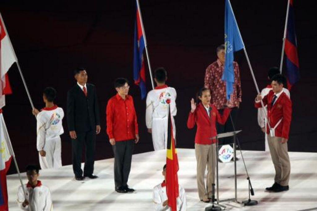 IKRAR ATLIT: Srikandi bola jaring, Mickey Lin (depan), mendapat penghormatan memimpin acara melafaz ikrar atlit dengan diperhatikan Menteri Kebudayaan, Masyarakat dan Belia, Encik Lawrence Wong (berbaju merah). - Foto THE STRAITS TIMES