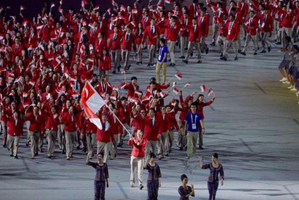 BERBARIS MASUK: Kontinjen Singapura yang didahului oleh pembawa bendera, perenang Quah Ting Wen, berbaris masuk ke stadium di upacara pembukaan penuh gemilang malam tadi. - Foto THE STRAIT TIMES