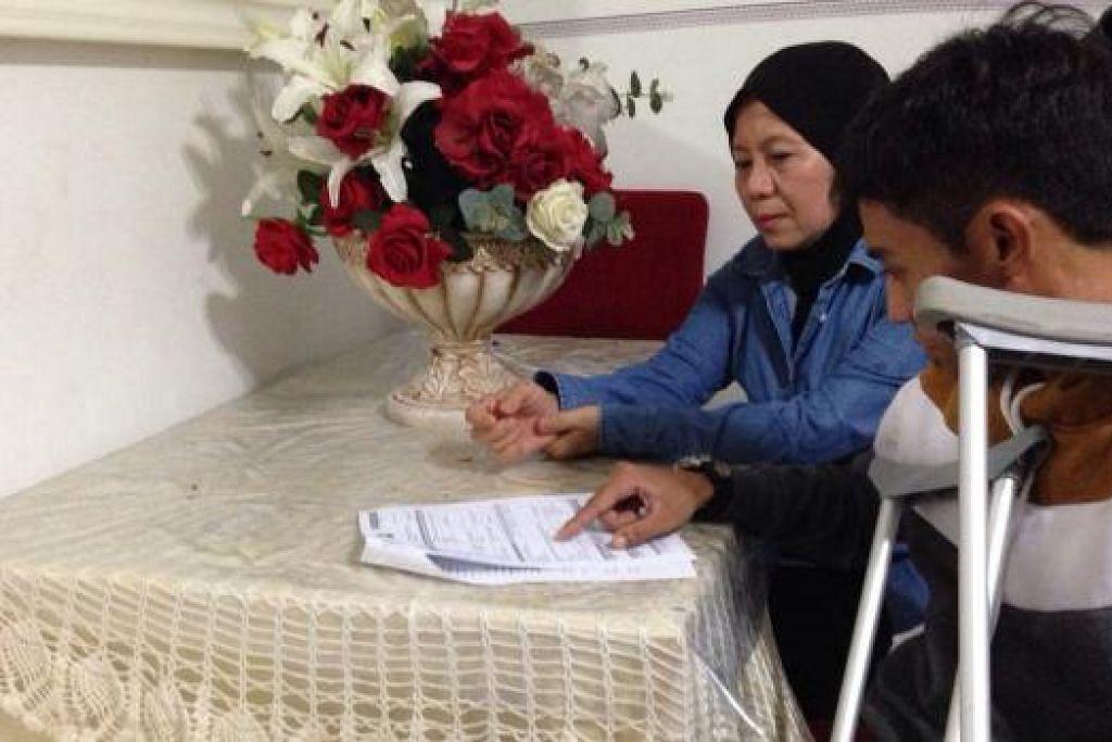 MANGSA LANGGAR LARI: Encik Abdullah Ali mengalami kemalangan langgar lari di kawasan Punggol pada Februari lalu semasa beliau dalam perjalanan pulang daripada tempat tugas. Di sebelah Encik Abdullah ialah ibunya, Cik Laili Abu Samah. - Foto ihsan ABDULLAH ALI