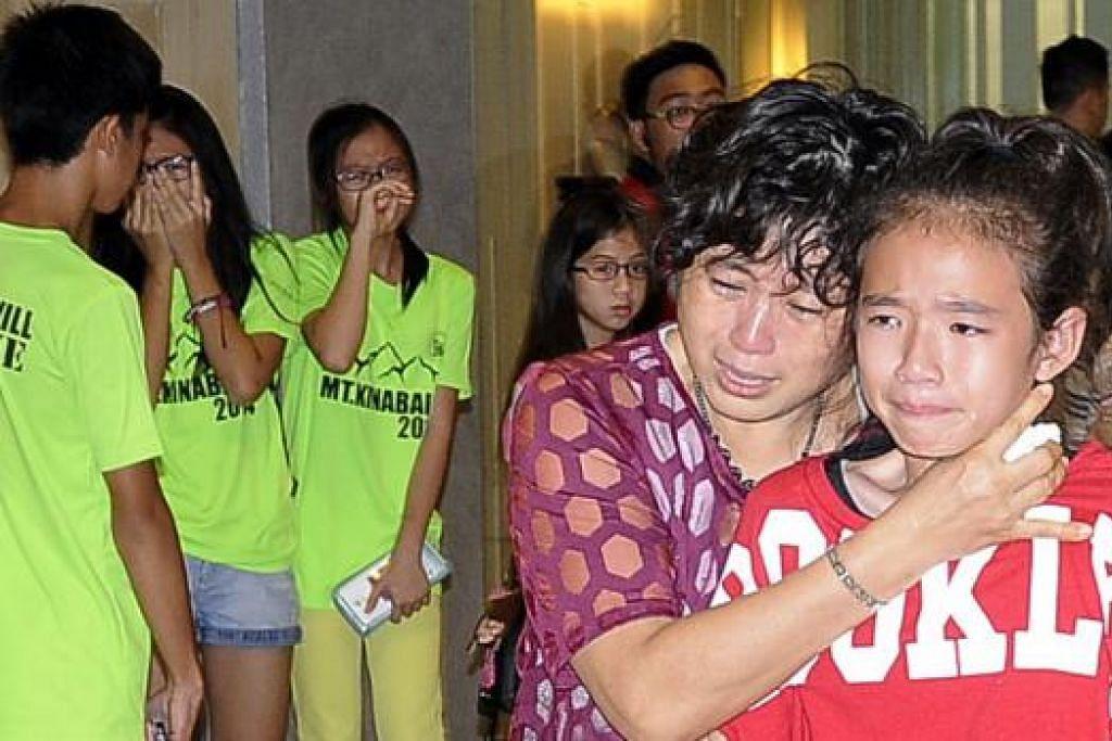 LEGA: Pelajar ini, yang baru pulang dari Kota Kinabalu semalam, dan anggota keluarganya tidak dapat menahan sebak di lapangan terbang. - Foto JOHARI RAHMAT