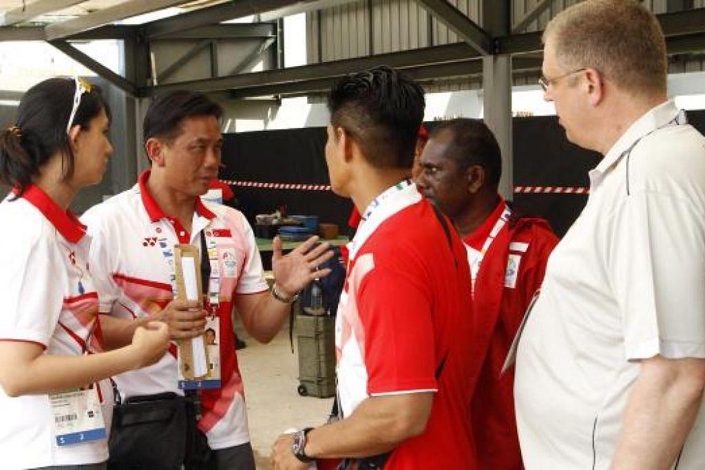 BERI KETERANGAN: Pegawai menembak Team Singapore Peter Teh (Dua dari kiri) berbual dengan pegawai menembak selepas penyertaan Goh Rui Huang dibatalkan.