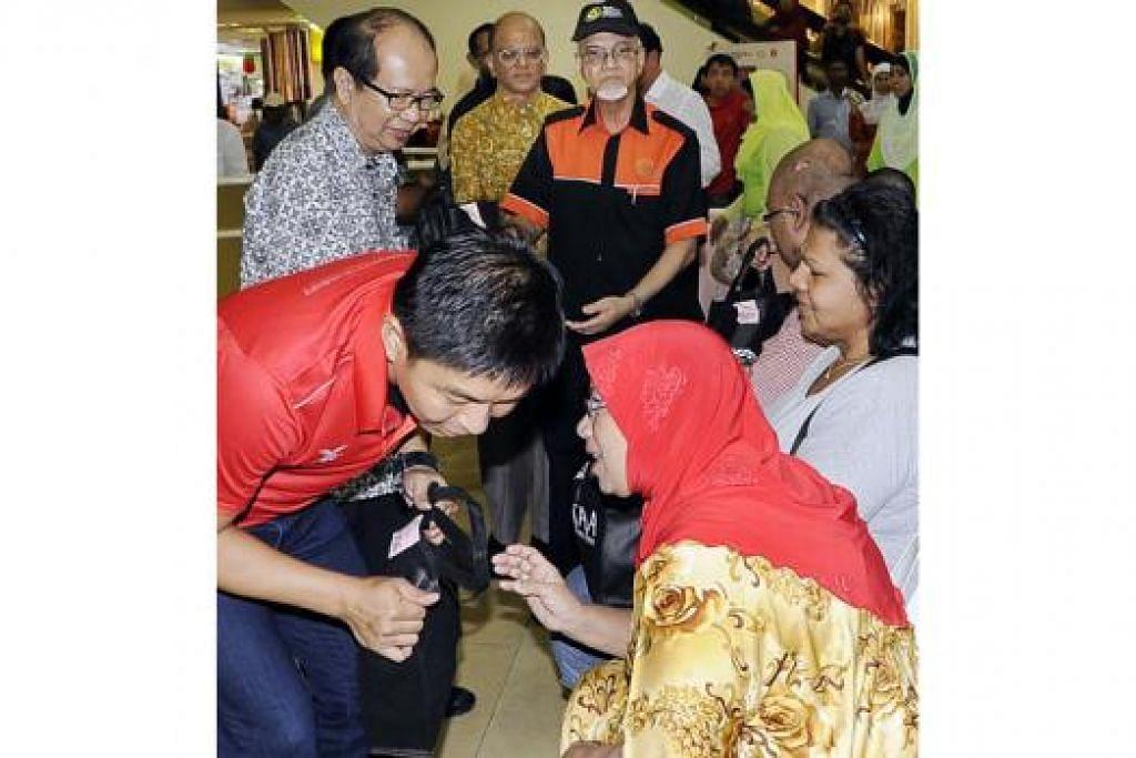 SEBAR KECERIAAN: Encik Tan Chuan-Jin mengagihkan beg hadiah kepada 30 keluarga kurang bernasib baik di majlis pelancaran kempen dana TAA semalam. - Foto JOHARI RAHMAT