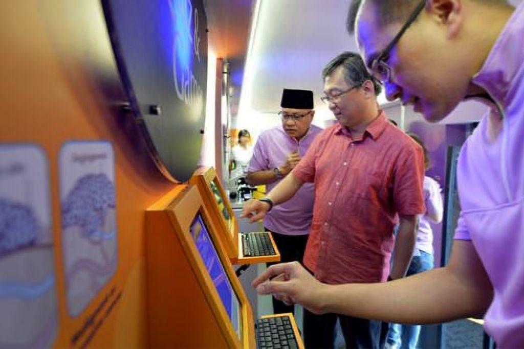RAIH PENGETAHUAN DALAM BAS: Encik Gan Kim Yong (tengah) mencuba multimedia yang disediakan di dalam bas semalam. - Foto M.O. SALLEH