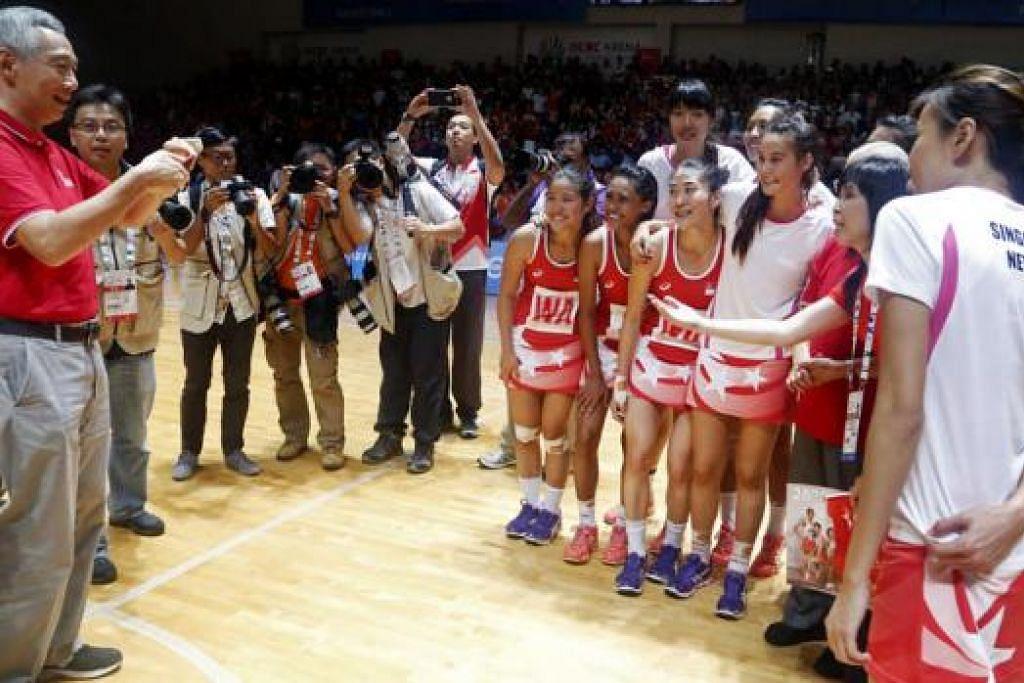 SAAT BANGGA: PM Lee (kiri) berkongsi kegembiraan pasukan bola jaring nasional, memetik gambar dan beramah-mesra dengan pemain di gelanggang selepas perlawanan berakhir. - Foto SINGSOC/REUTERS
