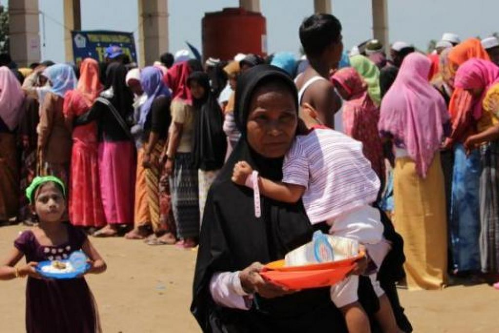 HARAPKAN BELAS IHSAN WARGA DUNIA: Seorang wanita Rohingya dilihat membawa pinggan di kem pendatang Rohingya dan Bangladesh di Kuala Cangkoi, Aceh, awal bulan ini. - Foto AFP