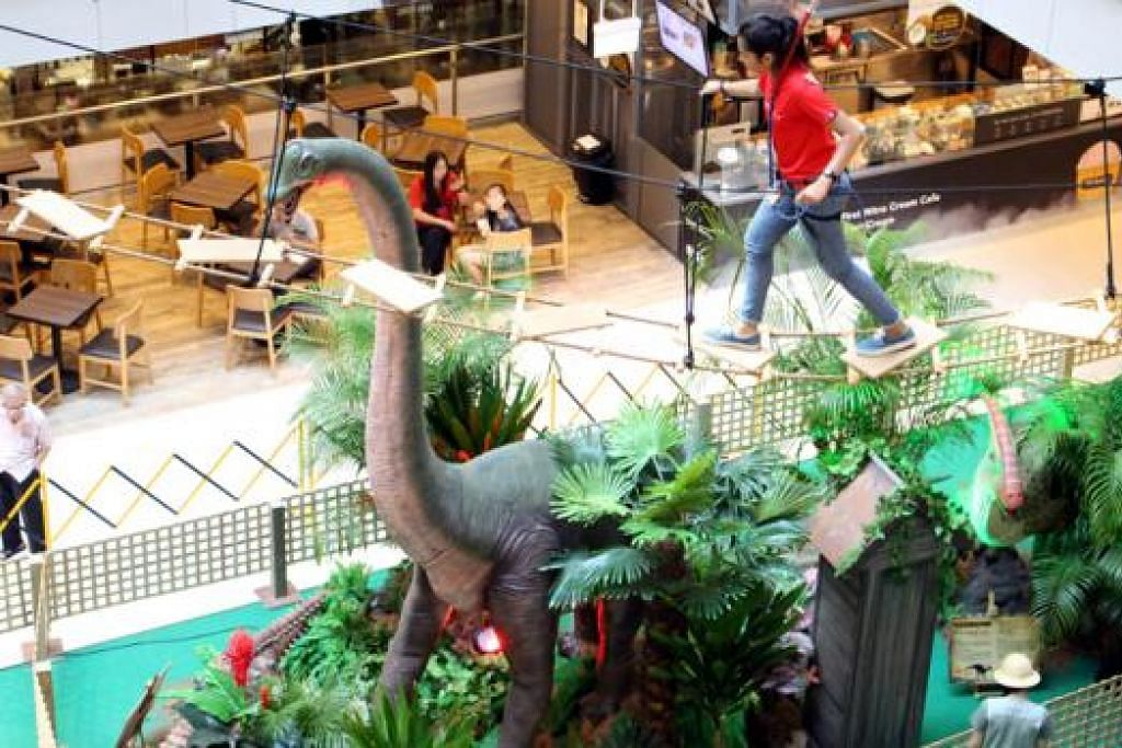 MENGATASI RASA TAKUT PADA KETINGGIAN: Seorang peserta melalui 'plank walk' yang terletak tinggi di atas pameran dinosaur dalam acara ONE-derful Jurassic Challenge. - Foto ONEKM MALL
