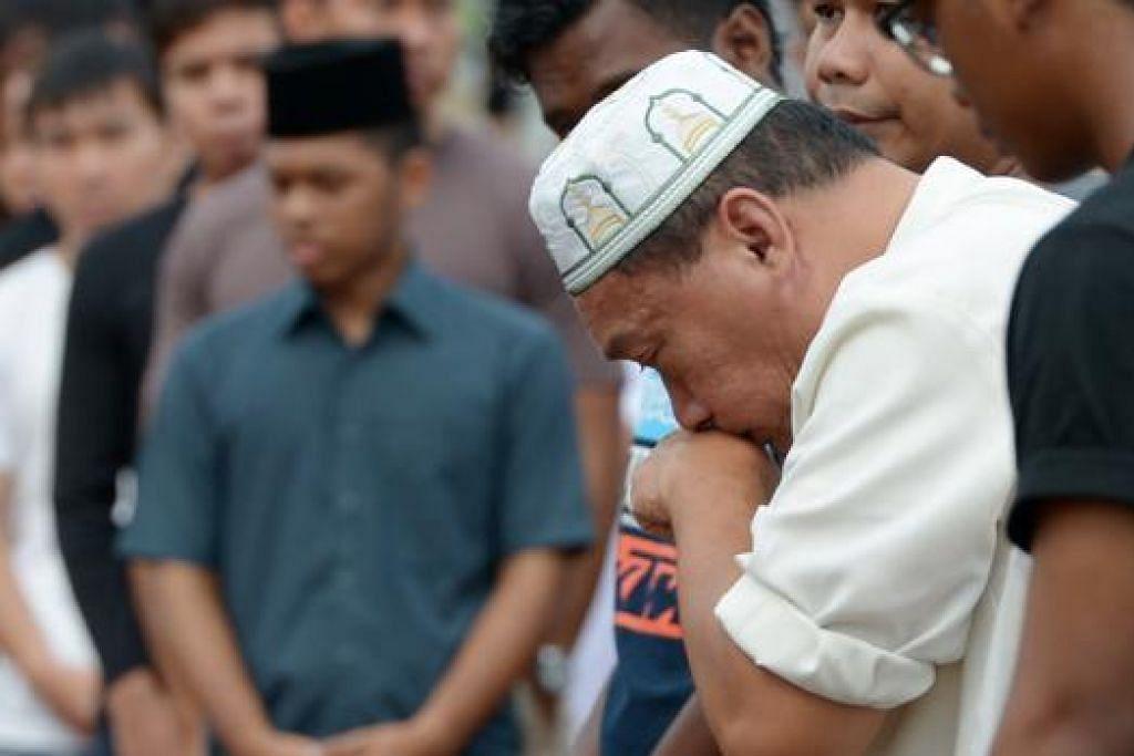 SAYU DAN HIBA: Bapa Allahyarham Daanish, Encik Amran, tidak dapat menahan sebak selepas jenazah dikebumikan di Pusara Abadi semalam. - Foto TUKIMAN WARJI