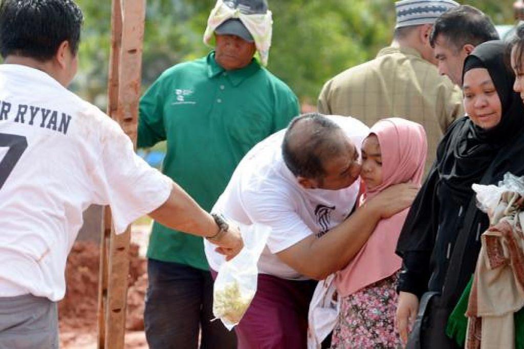 SELAMAT TINGGAL BUAT SELAMANYA: Ibu Allahyarham Ameer Ryyan Mohd Adeed Sanjya (dua dari kanan) berlinangan airmata semasa pengebumian di Pusara Abadi semalam. - Foto TUKIMAN WARJI