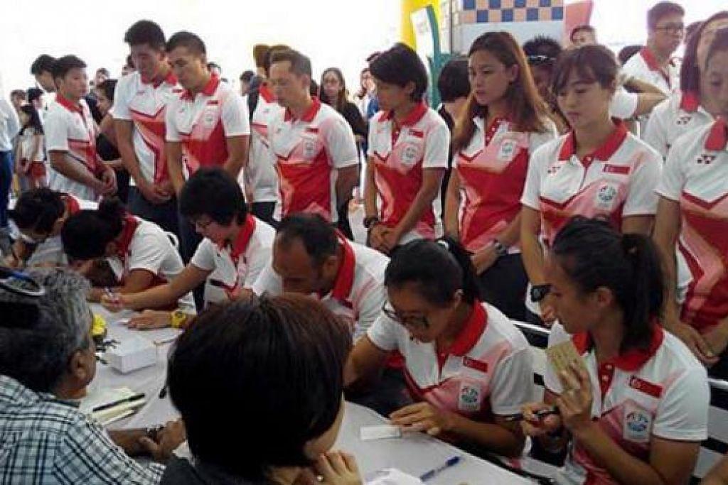 ANTARA YANG HADIR: Anggota kontinjen Sukan SEA turut melawat Sekolah Rendah Tanjong Katong untuk menulis nota takziah. - Foto THE STRAITS TIMES
