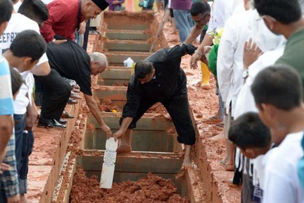 SELAMAT TINGGAL ANAKKU: Bapa Allahyarham Ameer Ryyan, Encik Mohd Adeed Sanjay, memacakkan nisan di kubur anaknya di Pusara Abadi semalam. Turut dikebumikan semalam ialah pemandu kembara, Allahyarham Muhammad Daanish. - Foto-foto TUKIMAN WARJI, SHIN MIN, THE STRAITS TIMES