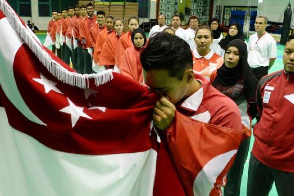 IKRAR SATRIA: Kapten pasukan silat nasional, Shakir Juanda, mengucup bendera negara dengan disaksikan rakan sepasukan dalam acara penyampaian bendera di Pusat Kecemerlangan Persisi minggu lalu. - Foto TAUFIK A. KADER