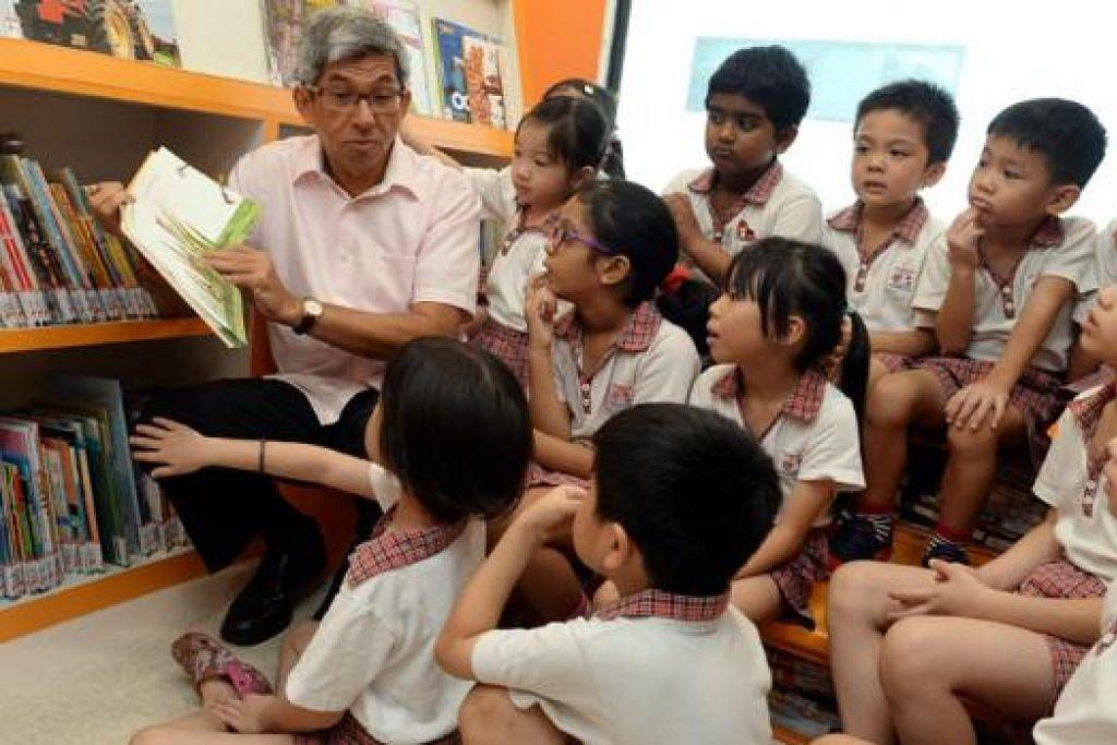 SESI BERCERITA: Dr Yaacob Ibrahim meluangkan masa membaca buku bersama kanak-kanak prasekolah di bas Mini-Molly semalam. - Foto TAUFIK A. KADER