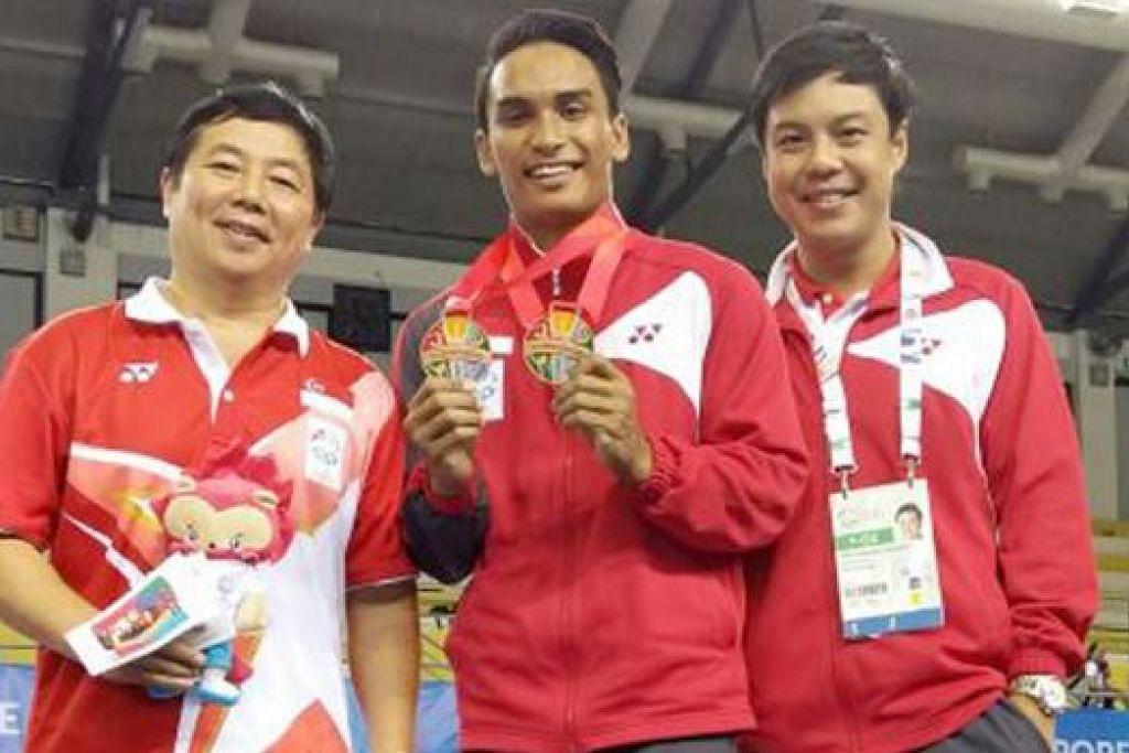 MEMBERANGSANGKAN: Peserta gimnastik, Aizat Muhammad Jufrie (tengah) menunjukkan dua pingat gangsa yang dimenanginya di Sukan SEA ini. Bersama beliau ialah jurulatih nasional Lin Zhenqiu (kiri) dan pengurus pasukan gimnastik Singapura, Janssen Ong. - Foto SINGAPORE GYMNASTIC