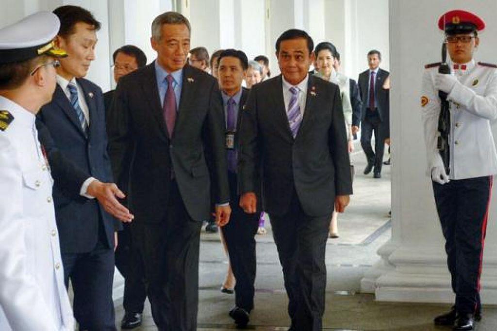 LAWATAN PM THAI: Jeneral Prayut, yang kelihatan bersama Encik Lee, berada di Singapura untuk lawatan pengenalan dan Rahat Pemimpin Singapura-Thailand. – Foto THE STRAITS TIMES