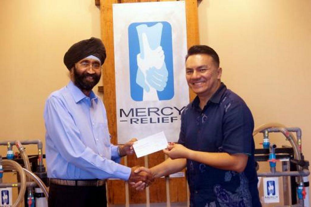 BANTU MANGSA GEMPA NEPAL: Penasihat Majlis Kebajikan Sikh, Encik Jagjit Singh (kiri), menyampaikan cek bernilai $30,000 kepada Naib Pengerusi Mercy Relief, Encik Suhaimi Rafdi, kelmarin. - Foto MERCY RELIEF