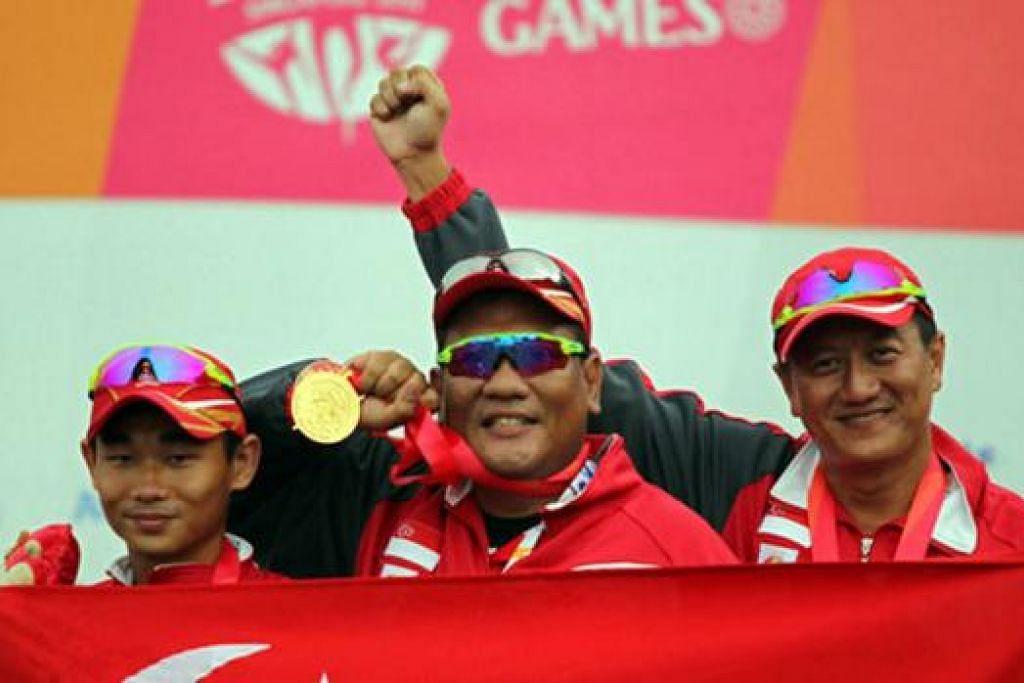 TEPAT KE SASARAN: Pasukan menembak 'trap' berpasukan, (dari kiri) Lin Hejun, Mohd Zain Amat dan Choo Choon Seng, meraikan pingat emas yang dimenangi semalam. - Foto REUTERS