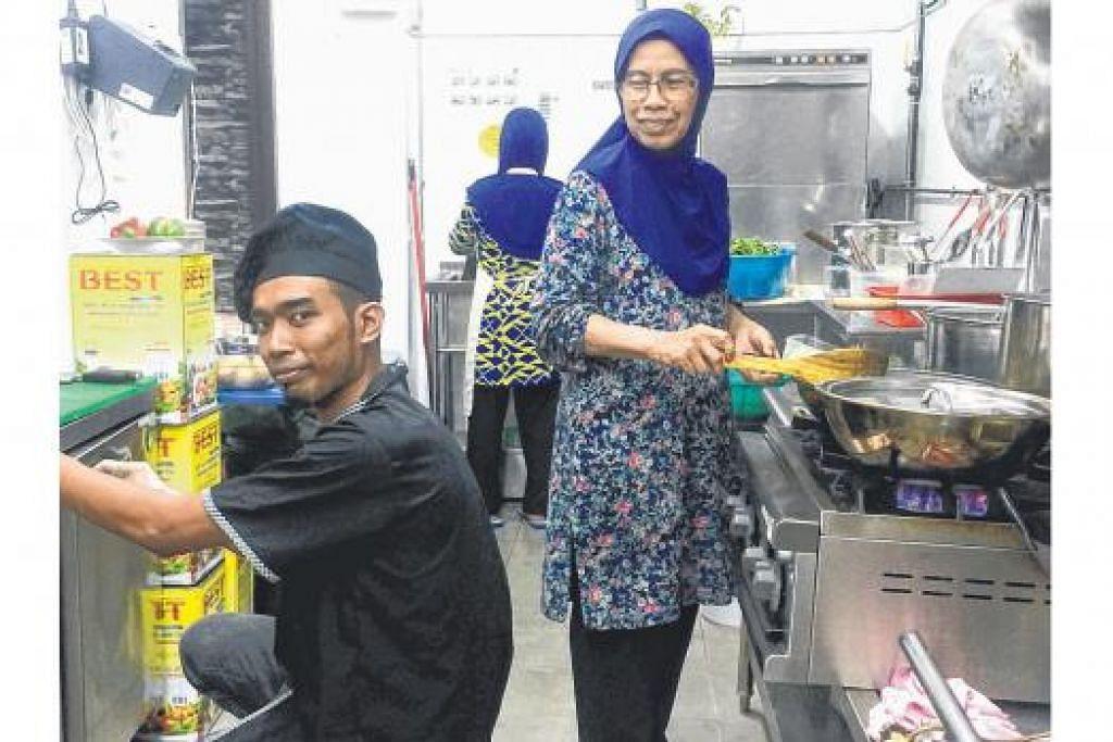 ORANG DAPUR: Cik Sukiah (kanan) menyelia kerja memasak yang disediakan di dapur Fiqk Culinaire. Bersamanya ialah salah seorang cef mereka, Encik Ariff Husyaire Ramley. - Foto-foto FARID HAMZAH