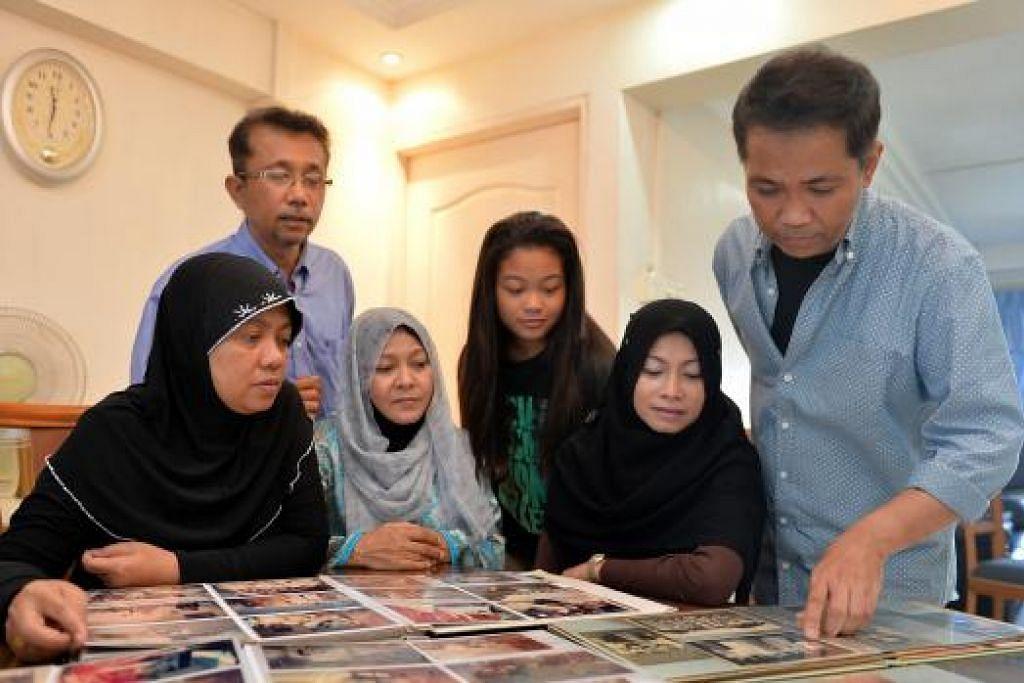 TATAP FOTO IBU BAPA: Encik Hamzah (berdiri, kiri) bersama ahli keluarganya, (dari kiri), adiknya, Cik Rozia; isterinya, Cik Halijah Othman; anaknya, Nabilah; adik iparnya, Cik Anizam Mokhtar; dan adik bongsunya, Encik Mustafa, melihat foto arwah orang tua mereka yang meninggal dunia selang dua hari pada bulan lalu. - Foto M.O. SALLEH
