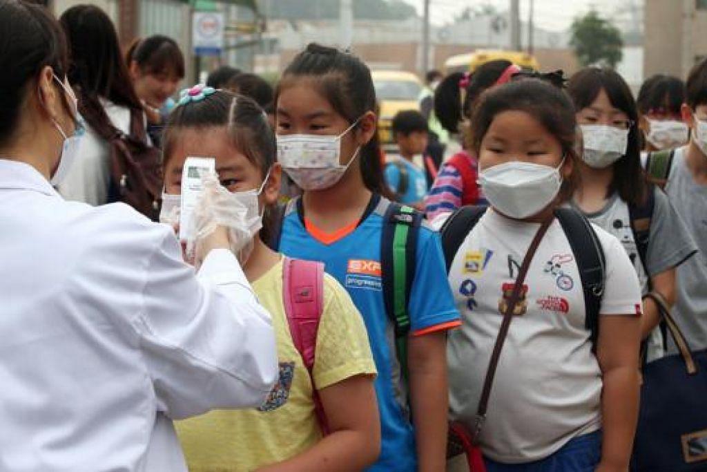 ANGKA KORBAN TERUS MENINGKAT: Seorang pekerja kesihatan memeriksa suhu badan kanak-kanak yang mengenakan pelitup di sebuah sekolah di Pyeongtaek, 65 kilometer ke selatan Seoul. - Foto AFP