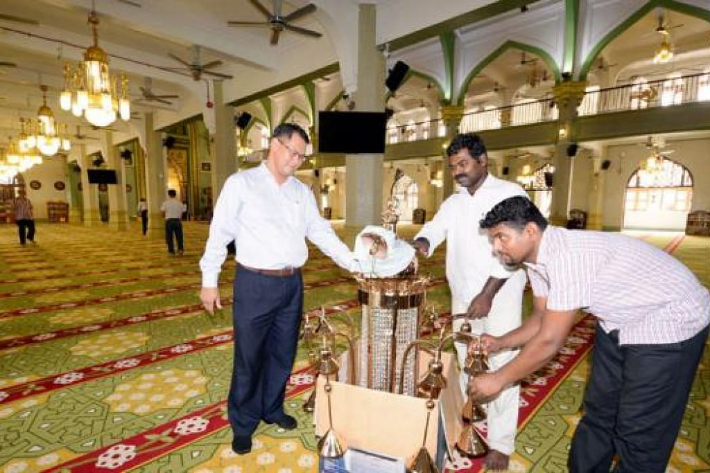 SINAR RAMADAN: Encik Zainal (kiri) bersama pekerja kontraktor yang sedang memasang lampu yang sudah dibersihkan dan digilap menjelang Ramadan.