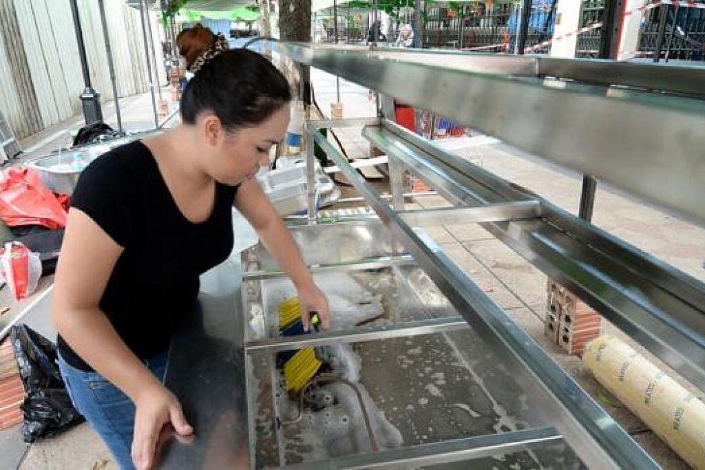 PEGERAI BAZAR SIAP SEDIA: Cik Maizurah sibuk menyiapkan gerainya di bazar Kampong Glam yang bakal menjual pelbagai manisan dan bubur pencuci mulut.