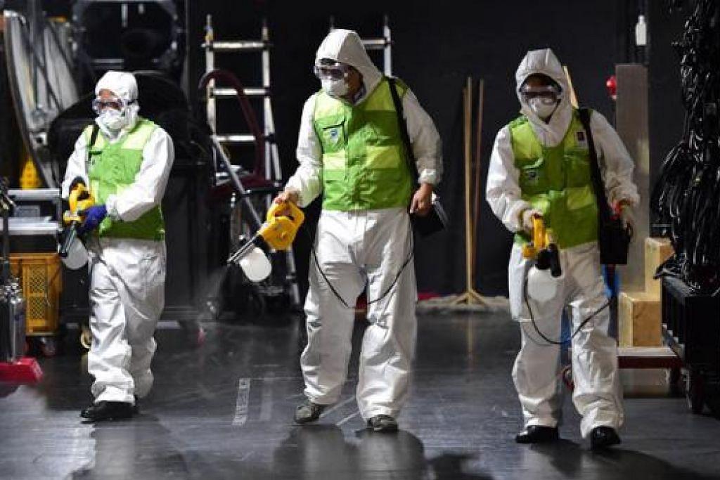 MEMBUAT KERJA-KERJA PEMBERSIHAN: Pekerja Korea Selatan yang mengenakan pakaian pelindung membersihkan teater di Pusat Budaya Sejong di Seoul. - Foto AFP