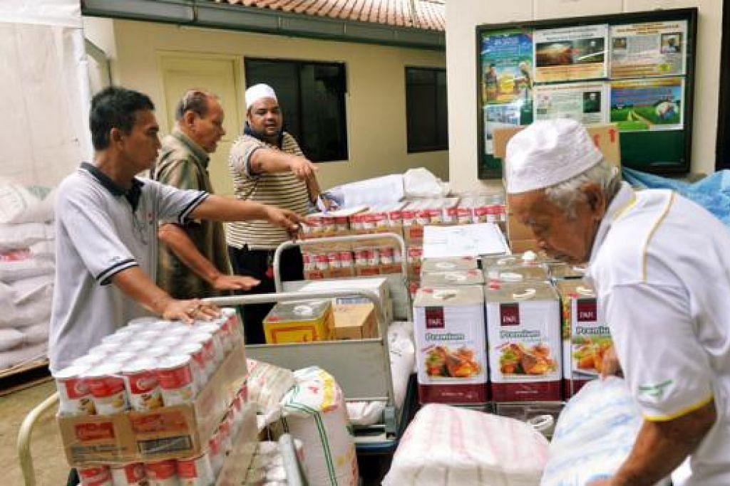 SIBUK DI DAPUR: Kakitangan dan sukarelawan Masjid Khalid memeriksa bekalan makanan untuk dijadikan juadah berbuka sepanjang Ramadan. - Foto KHALID BABA