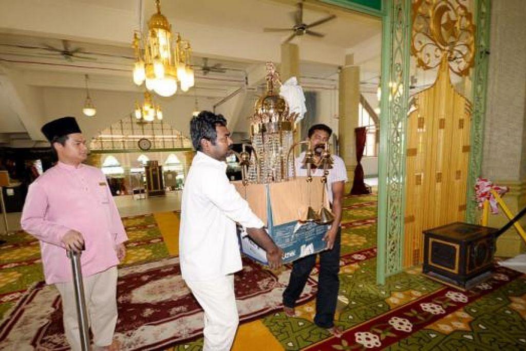 KILAUAN LAMPU RAMADAN: Beberapa pekerja kontraktor membawa masuk lampu berusia hampir sedekad di Masjid Sultan yang sudah digilap dan dibersihkan untuk menyambut Ramadan. - Foto JOHARI RAHMAT