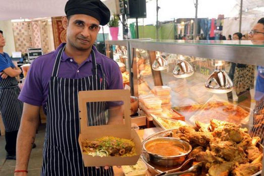 SAJIAN ISTIMEWA HOTEL: Seorang kakitangan Hotel Jen Tanglin menunjukkan hidangan nasi 'lamb shank' yang dijual di gerai bazar Ramadan di Woodlands. - Foto KHALID BABA