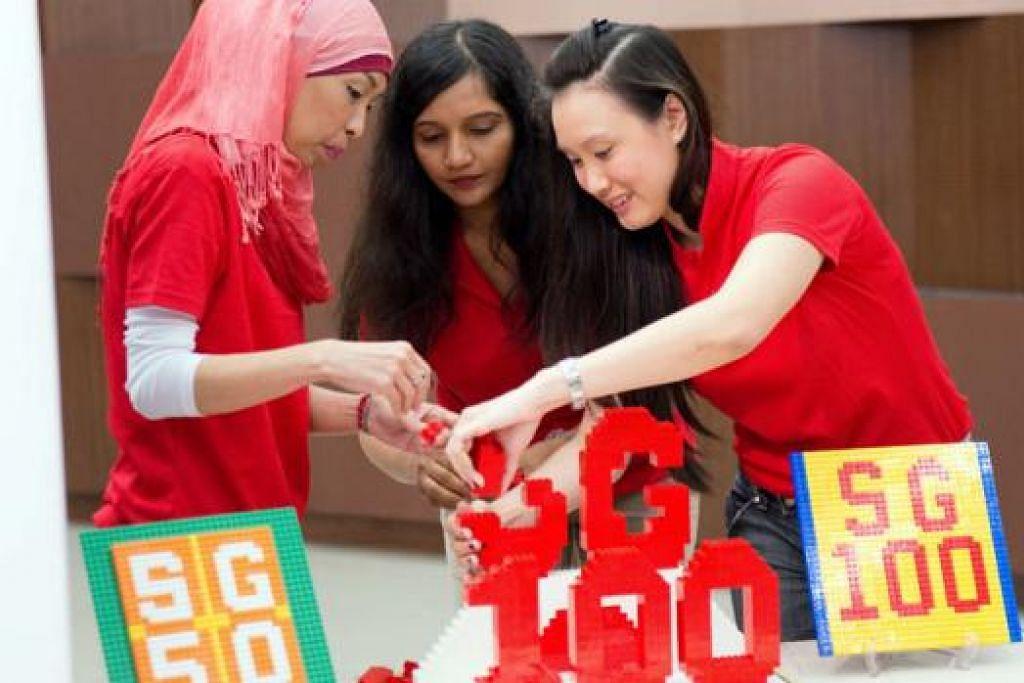 MEMBINA SINGAPURA BERSAMA: (Dari kiri) Cik Norizan, Cik Sheefal Sabharwal (Pengerusi Kelab Kesenian dan Kebudayaan Masyarakat (CACC) Punggol Central) dan Cik Rebecca Wong (Pengerusi CACC Punggol West) dengan struktur Lego yang antara kegiatan sempena hujung minggu jubli emas. - Foto PERSATUAN RAKYAT