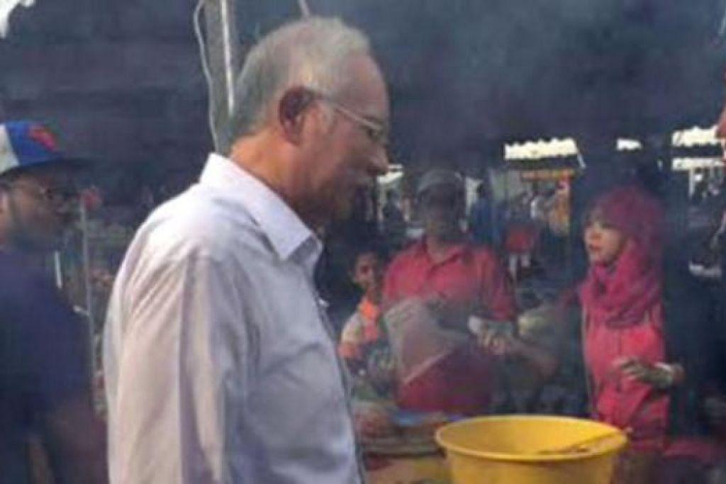 LIHAT AYAM PERCIK: Datuk Seri Najib mengunjungi kedai menjual ayam percik di Putrajaya kelmarin. - Foto TWITTER NAJIBRAZAK