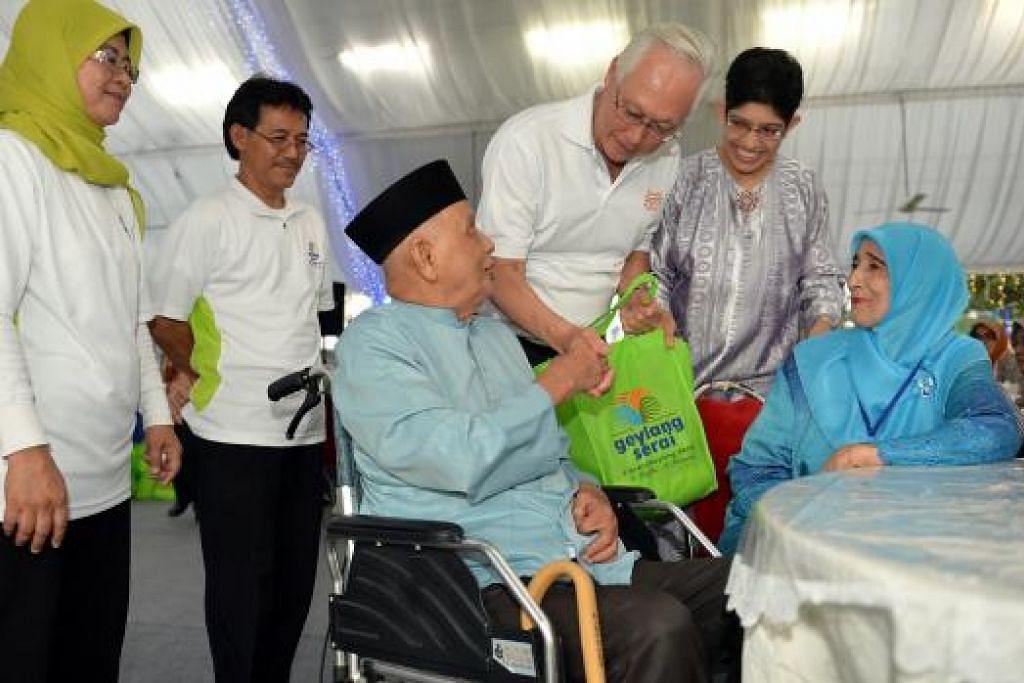 AGIH HABUAN: Profesor Madya Fatimah Lateef (dua dari kanan), bersama Menteri Kanan Emeritus Goh Chok Tong (tiga dari kanan), memberi habuan yang merangkumi antara lain beras, mi segera dan baucar pasar raya, kepada hampir 70 penduduk kawasan Geylang Serai semalam. - Foto M.O. SALLEH