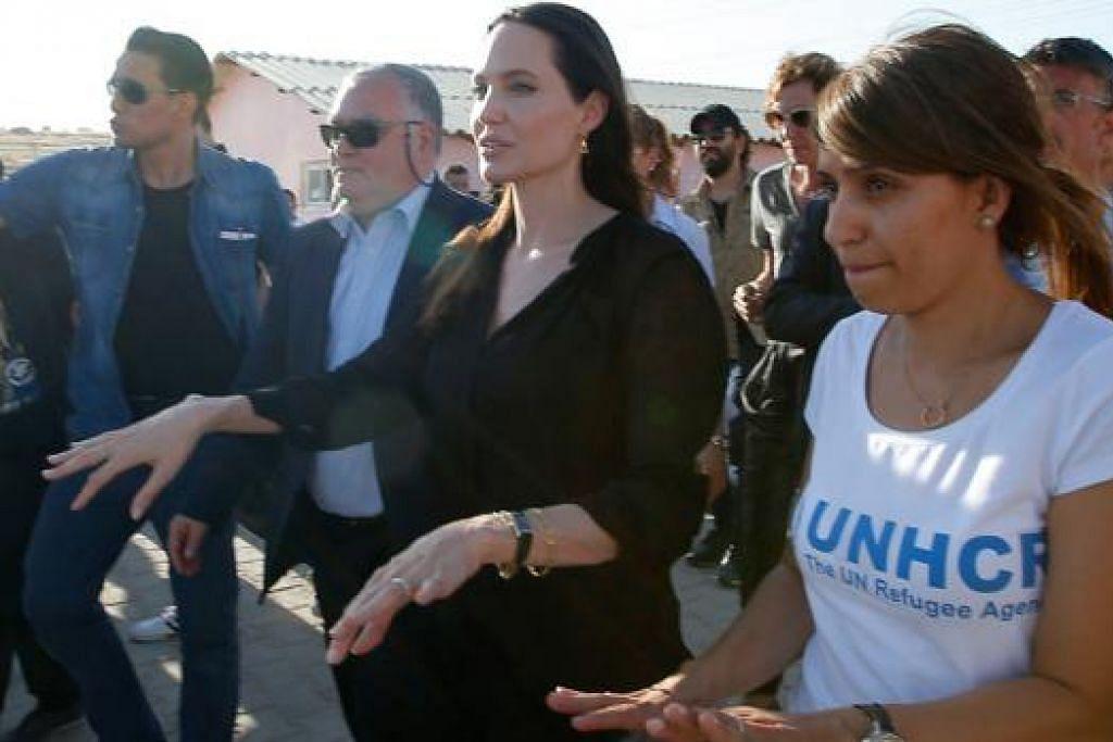 TINJAU KEADAAN: Pelakon terkenal Angelina Jolie (tengah) di kem pelarian Mardin, Turkey yang menempatkan mangsa perang di Syria. - Foto AFP