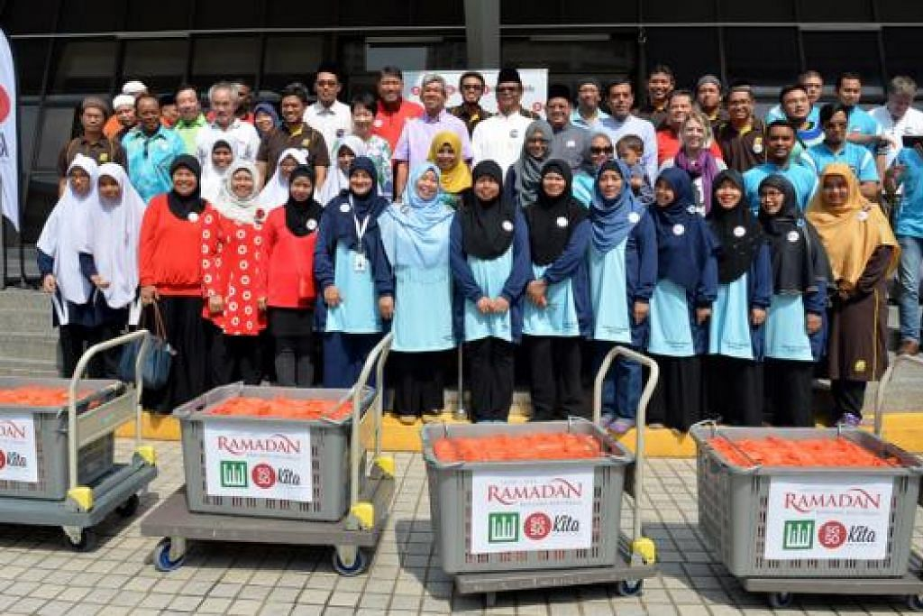 IMBAS KEMBALI MASA DI KAMPUNG: Hampir 50 sukarelawan masjid serta pelajar dari Madrasah Aljunied dan Sekolah Menengah Shuqun berganding bahu bagi menyiapkan dan mengagihkan bubur kepada penduduk di kejiranan Masjid Al-Mukminin. - Foto M.O. SALLEH
