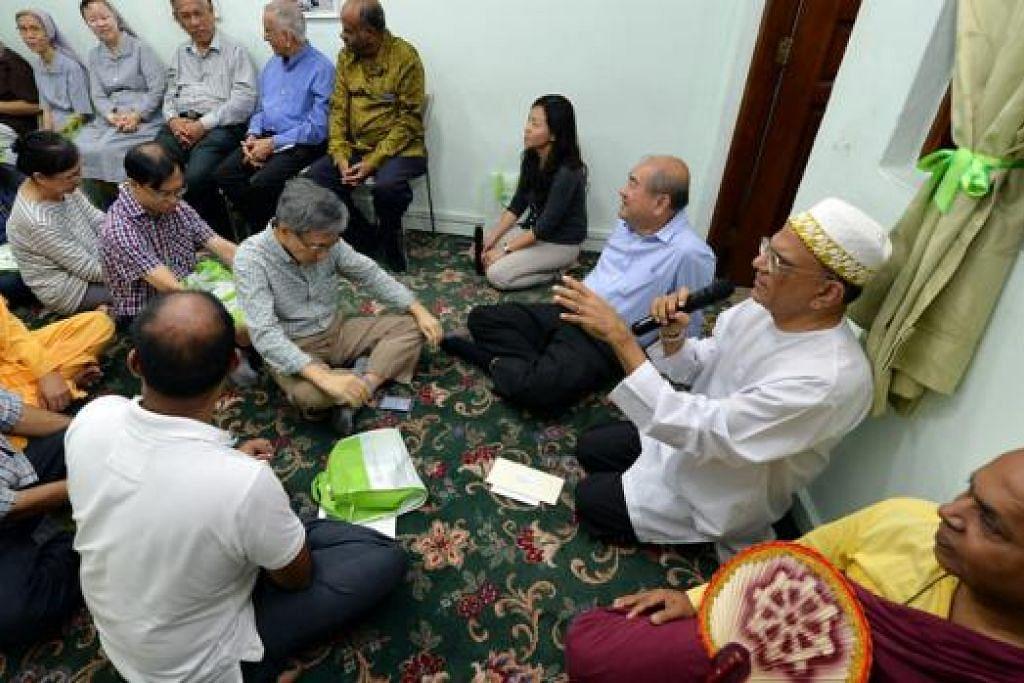 PENTINGNYA KEHARMONIAN KAUM: Encik Ameerali Abdeali (dua dari kanan) sedang bercakap kepada pemimpin pelbagai agama di majlis iftar Persatuan Bertindak Ginjal bagi Masyarakat Islam (MKAC). - Foto M.O. SALLEH