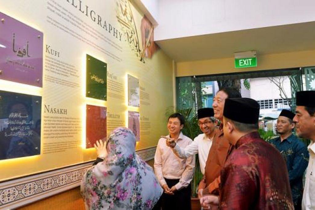 ERATKAN HUBUNGAN: Encik Teo (tengah, berbaju perang) bersama Dr Yaacob (tiga dari kiri) dan Haji Abdul Razak Maricar (kanan) menyaksikan antara pameran tentang seni khat Islam di Masjid Mujahidin sebelum mengikuti majlis iftar bersama jemaah. - Foto KHALID BABA
