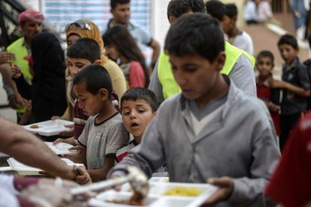 MANGSA PERANG: Pelarian Syria, termasuk kanak-kanak, beratur mendapatkan makanan di sebuah khemah pelarian Akcakale, dalam wilayah Sanliurfa di Turkey. - Foto AFP