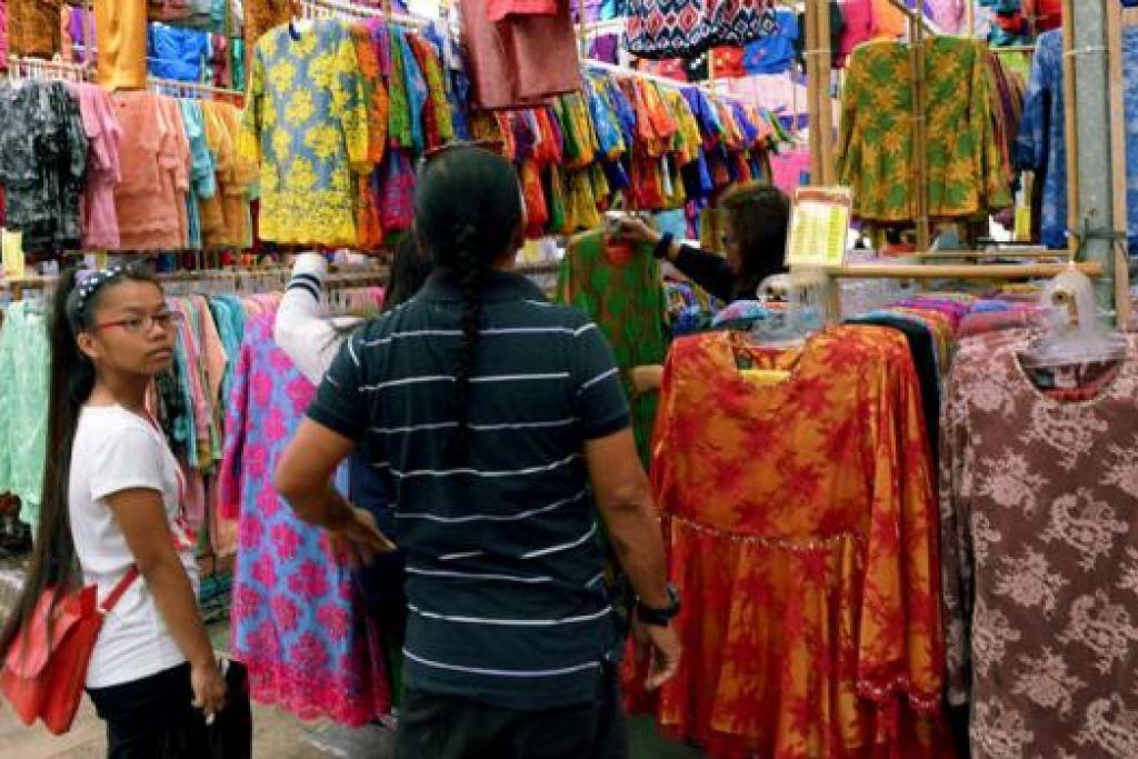 GHAIRAH MENANTI PELANGGAN DI LOKASI BARU: Gerai menjual baju kurung tradisional di tapak baru berdekatan dengan Stesen MRT Paya Lebar setelah lokasi dahulu dirobohkan awal tahun ini. - Foto TUKIMAN WARJI